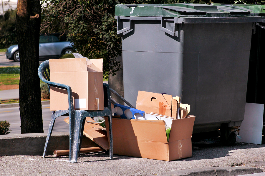 Waste left next to trash dumpster on the street. Cardboard boxes and old plastic chair near the container, trash dumpsters. Dirty refuse bins. Street scene. Recycling industry. Ecology. Not Ecology.