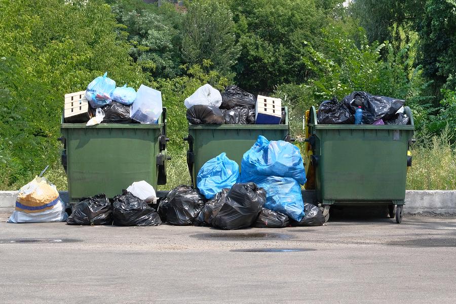 Dumpsters being full with garbage. Garbage is pile lots dump. Garbage waste lots junk dump.